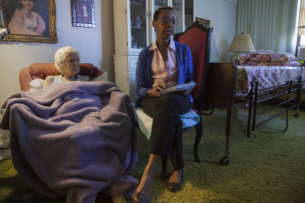 Heather sits with Florence, who was 100 years old when this photograph was taken. Whenever Heather enters a patient's home for the first time, she knows that she is walking into a long, long, complicated story that she understands nothing about, a story that is just then reaching its final crisis.