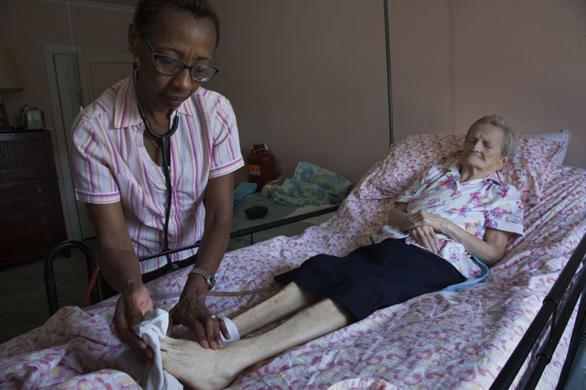 Heather assesses the pedal pulse of Ruth, a patient from Marine Park, Brooklyn. She was ninety-three years old when this photograph was taken.